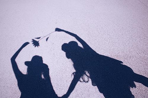 太陽の下、自分たちの影で遊ぶ双子の女の子たちのフリー写真素材(商用可)
