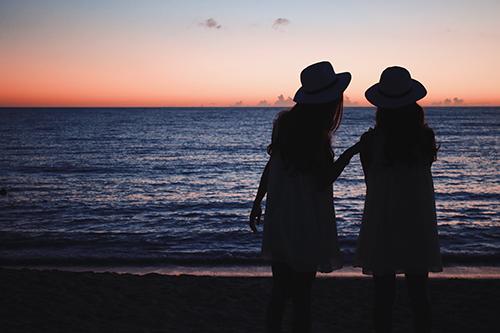 夕日が沈む海を見ながらおしゃべりしている双子の女の子たちのフリー写真素材(商用可)
