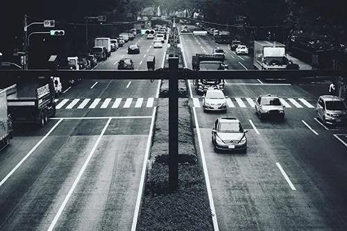 まっすぐに続く道を行き交う東京の車たちのフリー写真素材(商用可)