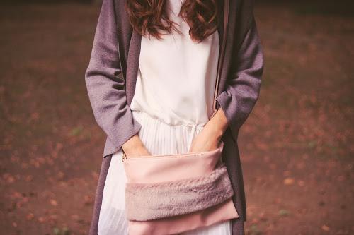 ふわふわハンドルクラッチバッグをゴソゴソしている女の子のフリー写真素材(商用可)