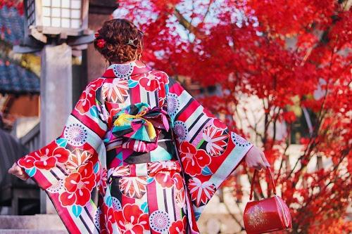 紅葉にはしゃいで神社の階段を駆け上がる着物の女の子のフリー写真素材(商用可)