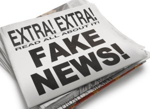 "The front page of a newspaper with the headline ""Fake News"" which illustrates the current phenomena. Front section of newspaper is on top of loosely stacked remainder of newspaper. All visible text is authored by the photographer. Photographed in a studio setting on a white background with a slight wide angle lens."