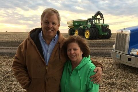 Terry and Janice Wanzek_in harvested field_combine in background