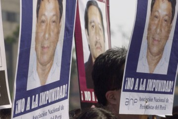 "A group of journalism students march to mark World Press Freedom Day in front of the Justice Palace, in Lima, Peru, on Monday, May 3, 2004. The placards show the faces of Peruvian journalists killed in the provinces after they wrote investigative articles.  ""No impunity!"" the signs read.  (AP Photo/Martin Mejia)"