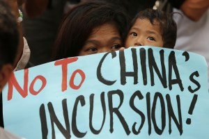 A Filipino protester holds a child as they join a rally outside the Chinese consulate at the financial district of Makati, south of Manila, Philippines on Tuesday, April 22, 2014. Photo credit: AP Photo/Aaron Favila