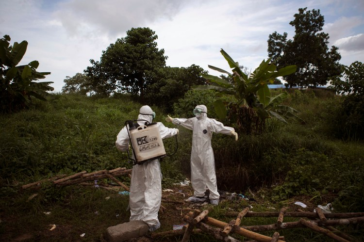 Healthcare workers spray each other with disinfectant after working inside a morgue with people suspecting of dying from the Ebola virus, in Kenema, Sierra Leone,  Sept. 25, 2014. (AP Photo/ Tanya Bindra)