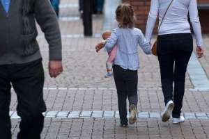 A young girl holds a doll as she walks hand in hand with a woman in Rotherham, Yorkshire, Britain, Aug. 27, 2014. An inqury report released 26 August claims that at least 1,400 children were sexually exploited in the city between 1997 and 2013.  (EPA/WILL OLIVER)