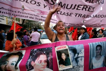 Norma Andrade, mother of Liliana Garcia Andrade, one of the women killed in the Mexican border city of Ciudad Juarez, carries an image of her daughter during a protest marking the International Women's Day in Mexico City, March 8, 2012. (AP Photo/Marco Ugarte)