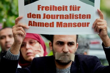 """A man holds a protest poster to support the release of the journalist Ahmed Mansour in Berlin, Germany, June 21, 2015. Mansour, 52, a senior journalist with the Qatar-based broadcaster Al-Jazeera, was detained at Tegel airport in Berlin on June 20 on an Egyptian arrest warrant, Al-Jazeera said. Poster reads: """"Freedom for the Journalist Ahmed Mansour"""". (AP Photo/Michael Sohn)"""