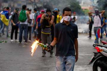 An opposition demonstrator prepares to throw a Molotov cocktail at police after clashes broke out at a protest in Caracas, Venezuela,  Feb. 12, 2015.  (AP Photo/Fernando Llano)