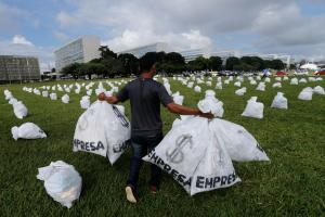 A member of the Clean Elections Movement carries bags representing money, during protest against the private financing of political campaigns, in front of the Brazilian National Congress, in Brasilia, Brazil, Tuesday, March 24, 2015. Approximately 200 bags were left in front of the National Congress in an attempt to mobilize civil society for political reform. (AP Photo/Eraldo Peres)