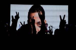 Supporters of television comedian and presidential candidate for the National Front of Convergence party Jimmy Morales, flash the victory sign in front of a screen at their party headquarters in Guatemala City, Sept. 6, 2015.  (AP Photo/Luis Soto)