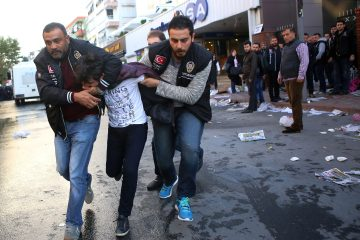 Police detain a youth as they surrounded the headquarters of opposition television stations and newspapers in Istanbul, Turkey, Oct. 28, 2015. Police in Istanbul  carried out a dawn raid at the building, using tear gas to enter the building of the company that owns opposition television stations Bugun TV and Kanal Turk, the Bugun and Millet newspapers and other business interests. (AP Photo/Mehmet Ali Poyraz, Cihan News Agency)