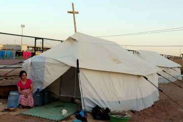 An Iraqi Christian refugee forced to flee Islamic State militants in Mosul, sits outside her tent in the Bahrka Refugee camp in Erbil, northern Iraq, Sept. 7, 2014. (EPA/Mohamed Messara)
