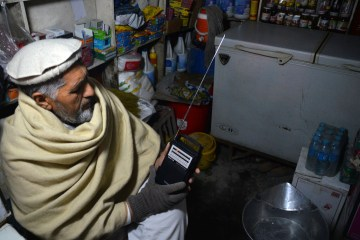 In this photo taken on Sunday, Jan. 10, 2016, an Afghan shopkeeper, listens to Islamic State Radio at his shop in Jalalabad, capital of Nangarhar province, Afghanistan. The Islamic State group in Afghanistan has adopted the media strategy of its mother organization in Syria and Iraq, including the production of grisly, professionally made videos showing battles and the killing of captives. But in impoverished Afghanistan, where few have access to the Internet, radio could prove more effective at recruiting fighters and silencing critics. (AP Photos/Mohammad Anwar Danishyar)