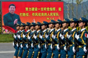 "Chinese troops practice marching near a billboard showing Chinese President Xi Jinping and the slogan ""Strive to build a People's Liberation Army that obeys the Party, Wins the war and has outstanding work style"" at a camp on the outskirts of Beijing,  (AP Photo/Ng Han Guan)"