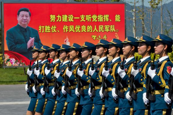 """Chinese troops practice marching near a billboard showing Chinese President Xi Jinping and the slogan """"Strive to build a People's Liberation Army that obeys the Party, Wins the war and has outstanding work style"""" at a camp on the outskirts of Beijing,  (AP Photo/Ng Han Guan)"""