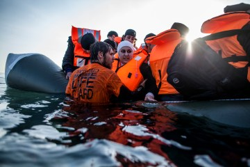 A Syrian refugee is helped by a volunteer to leave a sinking dinghy at a beach on the southeastern island of Lesbos, Feb. 28, 2016. Greece is mired in a full-blown diplomatic dispute with some EU countries over their border slowdowns and closures. Those border moves have left Greece and the migrants caught between an increasingly fractious Europe, where several countries are reluctant to accept more asylum-seekers, and Turkey, which has appeared unwilling or unable to staunch the torrent of people leaving in barely seaworthy smuggling boats for Greek islands.  (AP Photo/Manu Brabo)