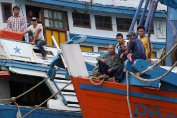 Foreign fishermen sit on their boats docked at the compound of Pusaka Benjina Resources fishing company in Benjina, Aru Islands, Indonesia, April 1, 2015.  (AP Photo/Dita Alangkara)