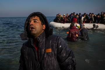 An exhausted man disembarks from a dinghy on a beach next to the town of Mytilene, after crossing a part of the Aegean sea from the Turkey's coast to the northeastern Greek island of Lesbos, on  Dec. 6, 2015.  (AP Photo/Santi Palacios)