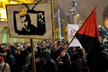 Protesters hold a banner depicting Prime Minister Viktor Orban as a king on TV during a demonstration against the government's new media law in Budapest,  Jan. 27, 2011.  (AP Photo/Bela Szandelszky)