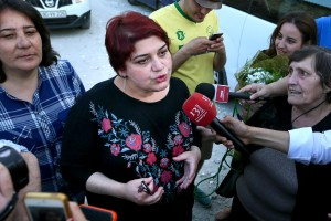 Khadija Ismayilova, center, a reporter for Radio Free Europe/Radio Liberty, who has become a symbol of defiance, praised by human rights and free-speech organizations around the world, speaks to journalists right after she has been released in Baku, Azerbaijan, May 25, 2016. (AP Photo/ Aziz Karimov)