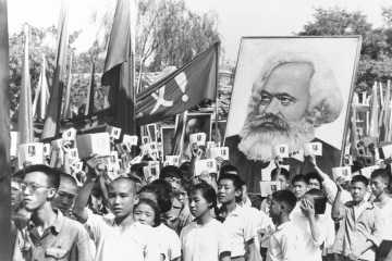 Youths are seen at a rally during the height of the Red Guard upheaval waving copies of the collected writings of Communist Party Chairman Mao Zedong, often referred to as Mao's Little Red Book and carrying a poster of Karl Marx, Sept. 14, 1966.  (AP Photo)
