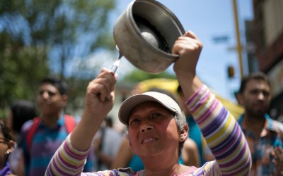 A woman bangs a pot to protest Venezuela's President Nicolas Maduro in Los Teques on the outskirts of Caracas, Venezuela, Sept. 7, 2016. Venezuelans are marching in cities across the country to demand authorities allow a recall referendum against Maduro to go forward this year. (AP Photo/Ariana Cubillos)