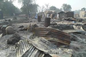 People walk past burnt out houses following an attack by Boko Haram in Dalori village, 5 km (3 miles) from Maiduguri, Nigeria, Jan. 31, 2016. A survivor hidden in a tree says he watched Boko Haram extremists firebomb huts and listened to the screams of children among people burned to death in the latest attack by Nigeria' s homegrown Islamic extremists. (AP Photo/Jossy Ola)