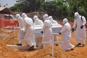 Health workers carry a body of a person that they suspected died from the Ebola virus at a new graveyard on the outskirts of Monrovia, Liberia, March 11, 2015.  (AP Photo/Abbas Dulleh)