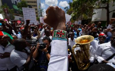 An activist wearing a beaded bracelet in the colors of the Kenyan flag holds his fist in the air as he and medical staff protest the detention of union leaders, outside an appeal court in Nairobi, Kenya, Feb. 15, 2017.  (AP Photo/Ben Curtis)