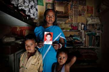 **HOLD  ADVANCE TO GO WITH STORY SLUGGED INDIA MISSING CHILDREN BY NIRMALA GEORGE** In this Monday, March 25, 2013, photo, Pinky Devi shows the picture of her son Ravi Shankar, who was disappeared in 2010.  Standing with her are sons Rahul, 7, left, and Ramesh,5, in their one room tenement, in New Delhi, India, March 2013.  (AP Photo / Manish Swarup)