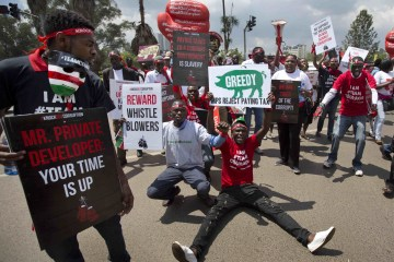Protesters sit down in the street during an anti-corruption demonstration in downtown Nairobi, Kenya Dec. 1, 2015. Over a hundred demonstrators marched to the Supreme Court, Parliament, and State House on Tuesday to protest against corruption. (AP Photo/Ben Curtis)