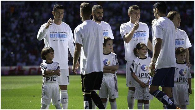 Real Madrid players standing with refugee kids as their club mascot (source: www.espnfc.com)