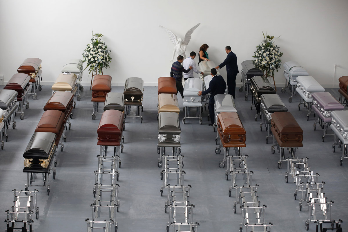 Funeral workers arrange coffins holding the remains of the victims who died in an accident of the plane that crashed into the Colombian jungle with Brazilian football team Chapecoense onboard, in Medellin, Colombia December 1, 2016. REUTERS/Jaime Saldarriaga