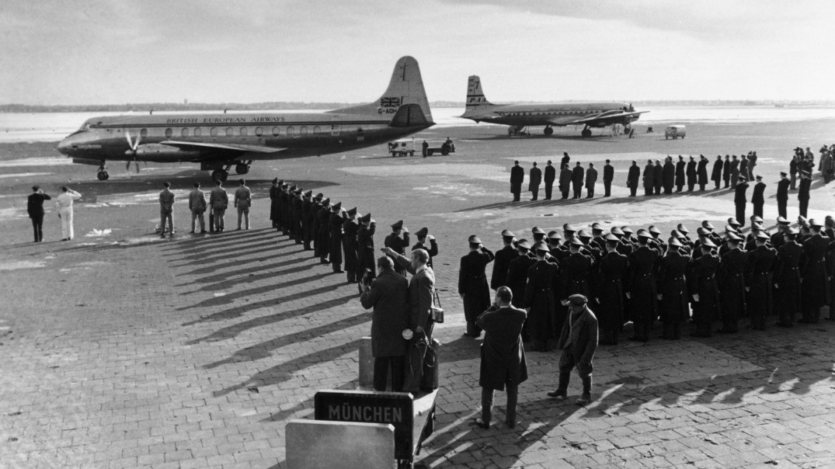 11th February 1958, The B,E,A, aircraft carrying the coffins of the victims of the crash at Munich in which 23 people died, eight being Manchester United footballers, about to leave Munich Airport to return to England as a West German police guard of honour salute. Photograph: Popperfoto/Getty Images