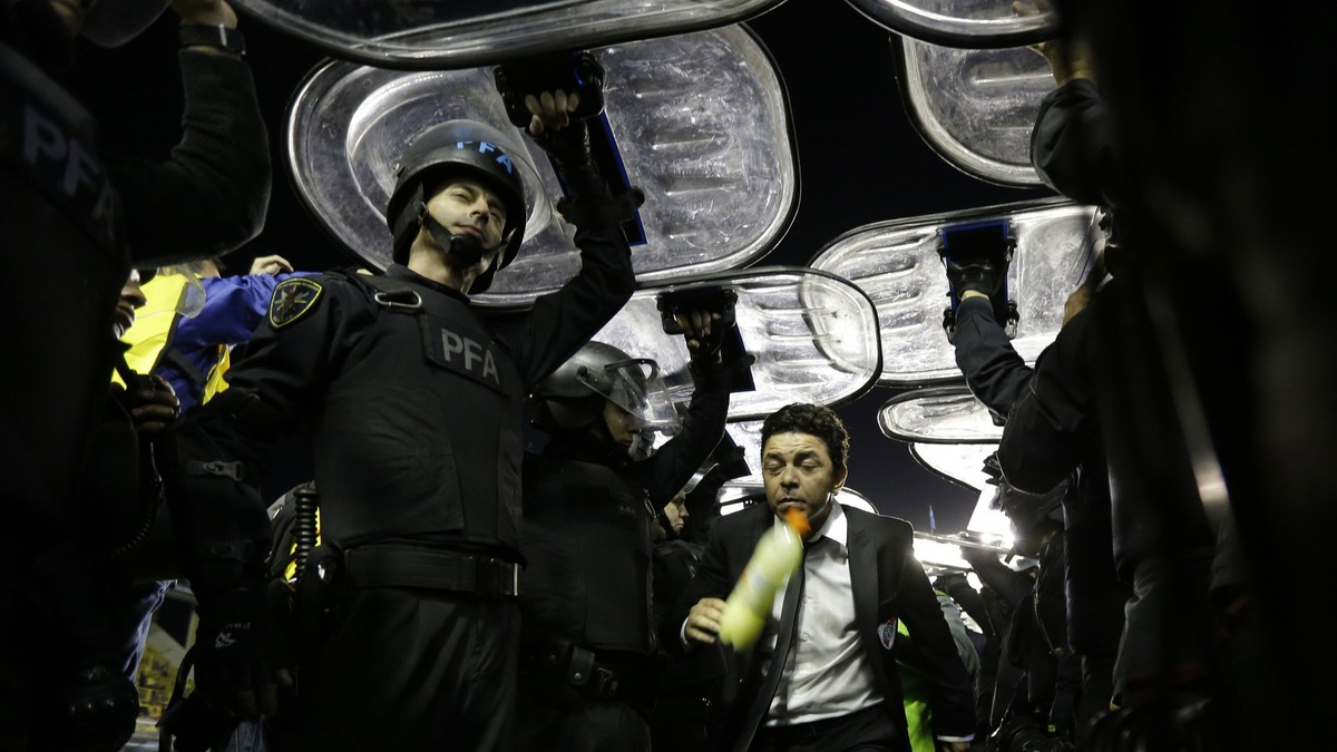 Marcelo Gallardo coach of River Plate, center, leaves the field protected by riot police. [Source: Mashable]