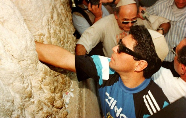 Argentinian soccer star Diego Maradona puts a note with a secret wish in between the stones of the Wailing Wall in Jerusalem's Old City 30 May. It's the third time that Maradona and the team come to the Wall before the World Cup finals. Argentina will play Israel 31 May in a friendly game. (Photo credit should read MENAHEM KAHANA/AFP/Getty Images)