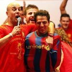 VIDEO & PICTURE: Cesc bundled into Barca shirt by Spain team-mates