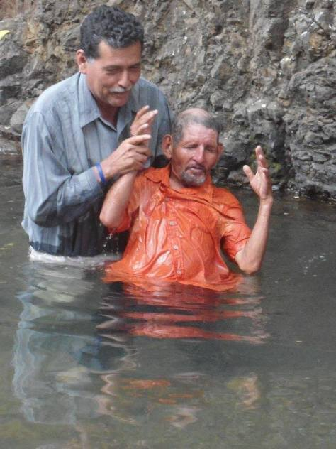 A man is baptized in the creek