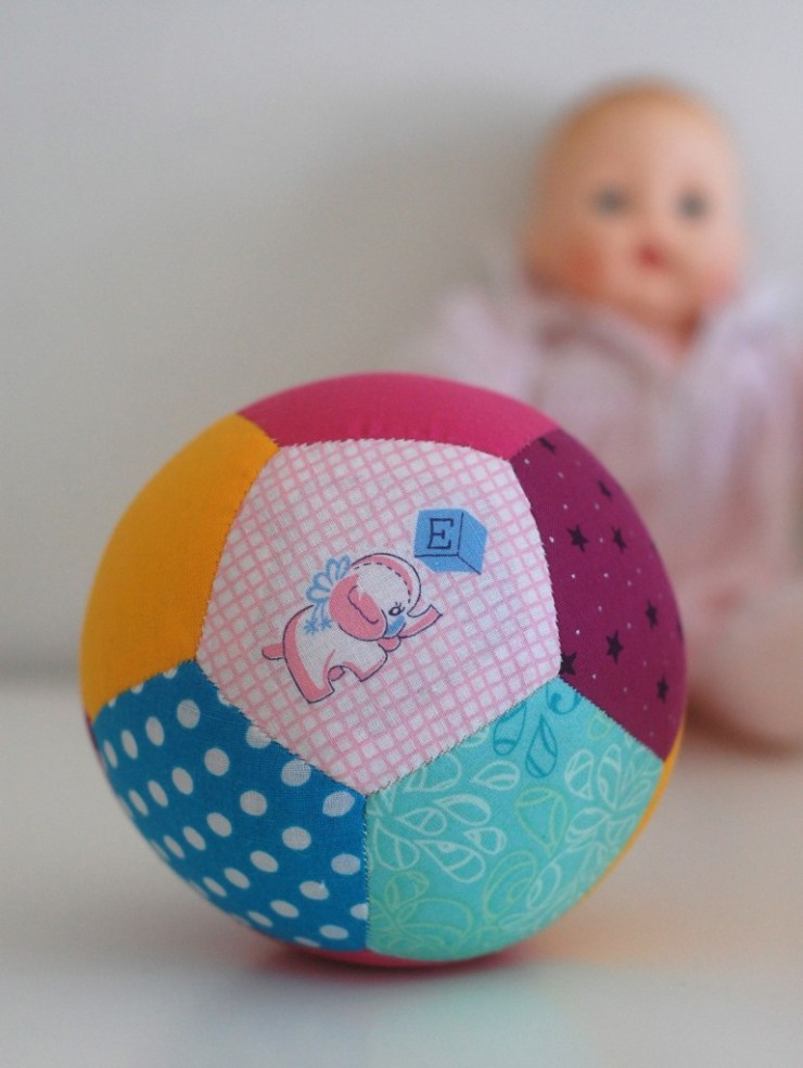 The DIY Patchwork Play Ball by While She Naps  features English Paper Piecing, lots of colors for baby and a fun rattle sound. -Sewtorial