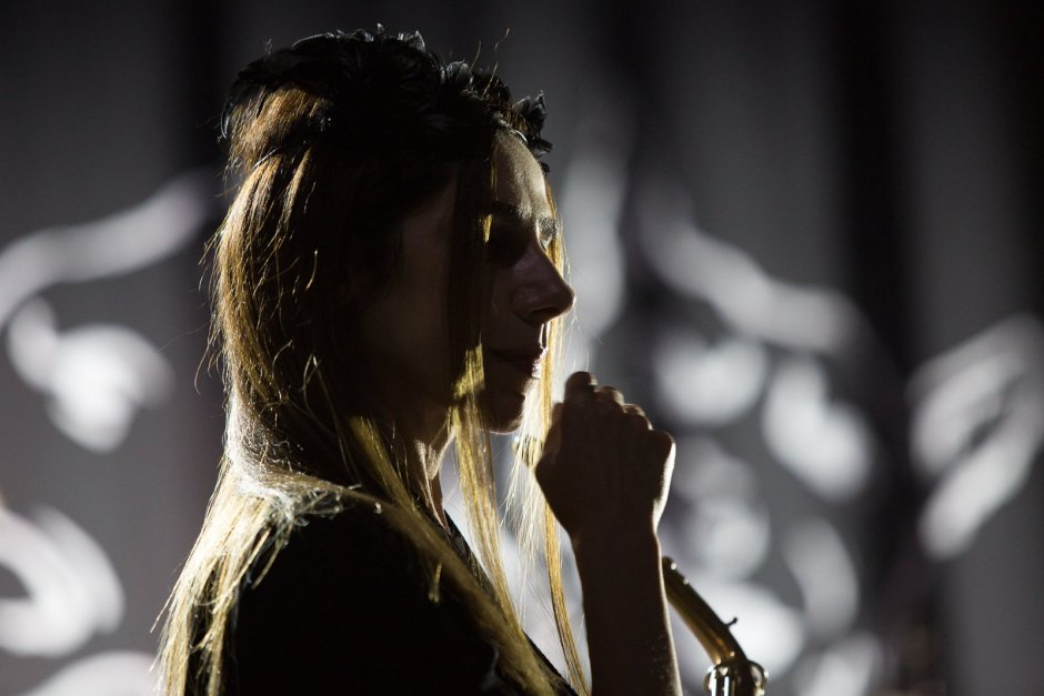A photo of PJ Harvey holding a microphone, backlit by white light