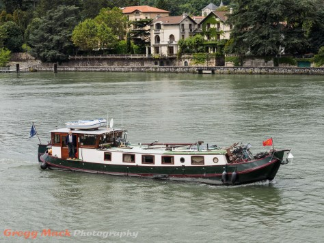 A houseboat passes by our docked river boat in Vienne.