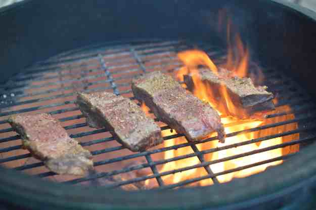 Beef Short Ribs Getting Seared Over Hardwood Lump Charcoal