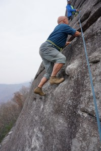 """Climber-historian Mike Fischesser tests the grip on Bob Watt's original klettershues, worn 50 years ago during the first ascent. Note his """"harness"""" as well."""