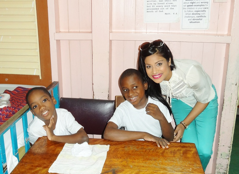 Miss Guyana India Katherina Roshana with two of the children at the Ptolemy Reid Rehabilitation Centre