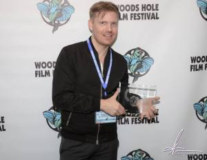 """Director Hunter Lee Hughes receiving the Audience Award for """"Guys Reading Poems"""" at the 25th annual Woods Hole Film Festival."""