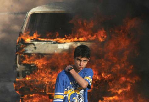 MOHAMMED ABED/AFP/Getty Images — A Palestinian youth stands in front of a burning vehicle during clashes between rival Fatah and Hamas in Gaza City, 14 May 2007. Two Palestinians were killed in fresh fighting between rival Fatah and Hamas gunmen today despite a truce aimed at ending the worst factional violence since a unity government took office.