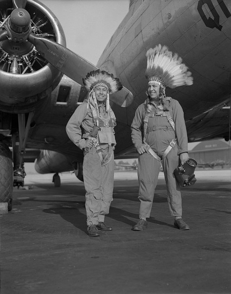 Gus Palmer (Kiowa, at left), side gunner, and Horace Poolaw (Kiowa), aerial photographer, in front of a B-17 Flying Fortress. MacDill Field, Tampa, Florida, ca. 1944.