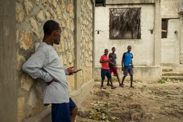 Watson listening to music on his cellphone. Dusk. Bois Jolie, Haiti. May, 2015.